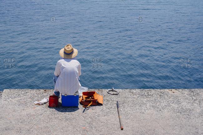 Fisherman sitting on a cooler at a pier in Fukuoka, Japan