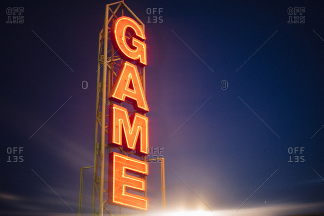 Neon game sign against a nighttime sky