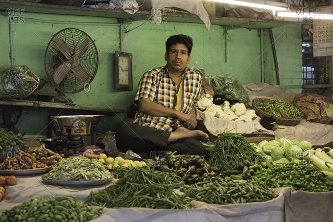 Man selling many types of vegetables and ingredients at a market in Bhavnagar, Gujarat, India