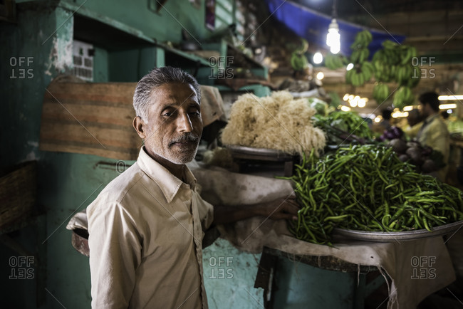 Man standing next to the vegetables he has for sale at a market in Bhavnagar, Gujarat, India