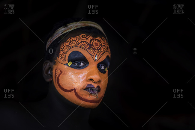 Dancer in traditional face paint performing in the Theyyam Festival Kerala, India