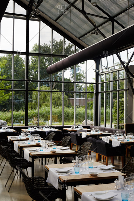 Amsterdam, Netherlands - July 4, 2015: Tables set in a greenhouse dining room