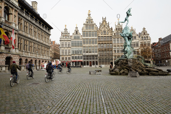 Antwerp, Belgium - November 4, 2014: Bicyclists ride past the Brabo Fountain in Antwerp, Belgium