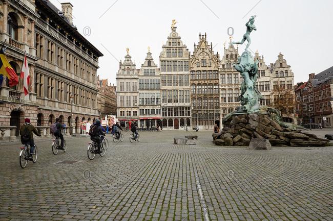 Antwerp, Belgium - November 4, 2014: Bicyclists ride past the Brabo Fountain in Antwerp, Belgium