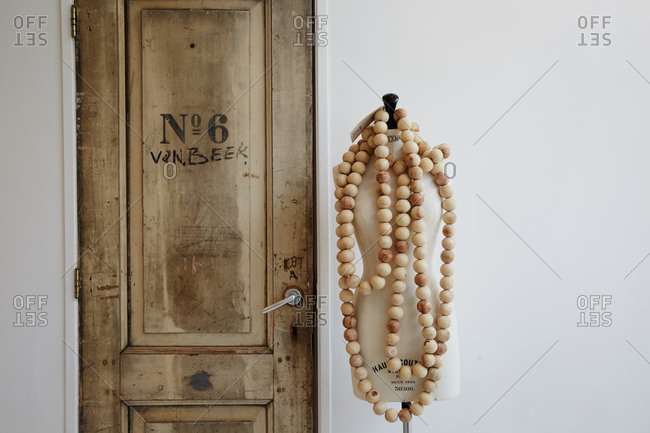 Amsterdam, Netherlands - July 5, 2015: Dress form draped with wooden beads standing next to a wooden door in shop