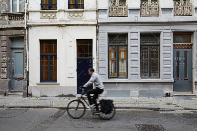 Man rides bicycle past buildings in Antwerp, Belgium