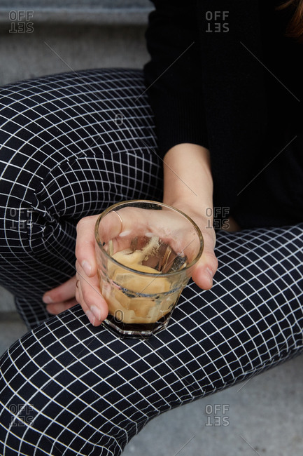 Person in grid-patterned pants holding glass of espresso
