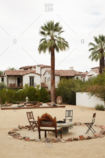 Chairs around an outdoor fireplace at a desert hotel in California