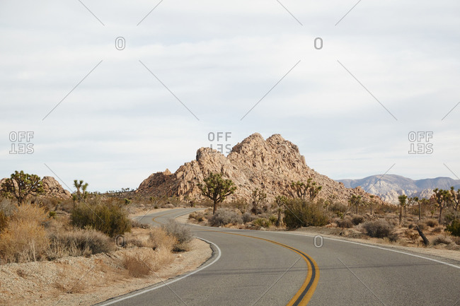 California desert highway winds past rock formations
