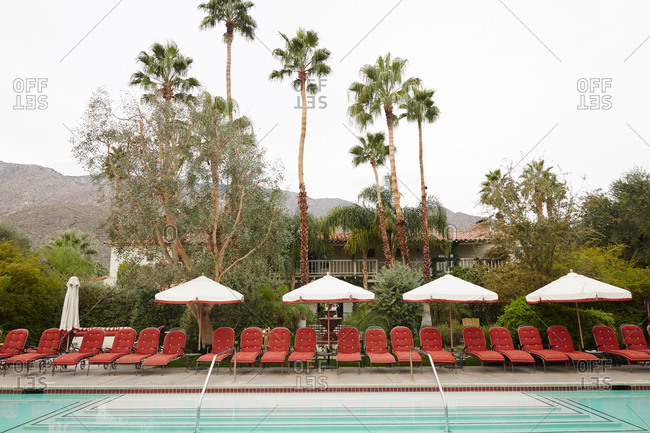 California, USA - January 26, 2015: Hotel pool lined with red chaise lounges in California desert