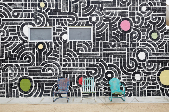 Vintage metal chairs against a patterned cinderblock wall