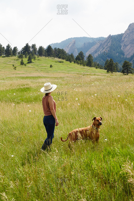 Woman in sun hat standing in field with dog