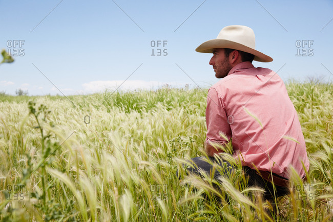 Colorado, USA - June 26, 2014: Portrait of man in cowboy hat crouched in field