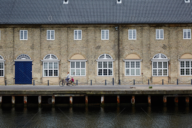 Copenhagen Denmark - June 28, 2015: Woman and child riding bicycles along a waterfront building in Copenhagen