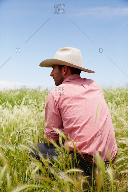 Colorado, USA - June 26, 2014: Man in cowboy hat crouching in long grass