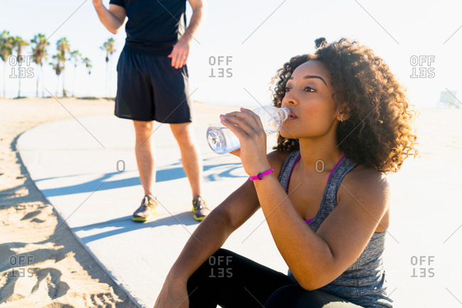 Mid adult woman, by beach, drinking from water bottle