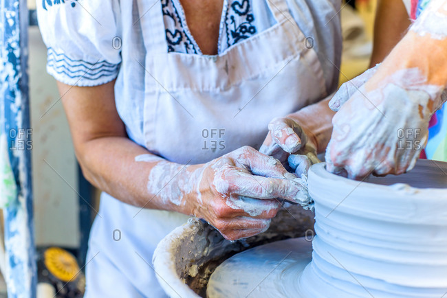 Close up of hands of female potter and mature student making pot on potters wheel