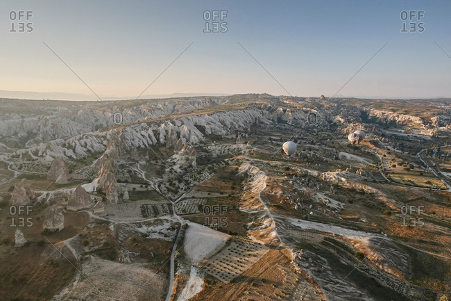 Distant view of hot air balloons over landscape, Cappadocia, Anatolia, Turkey