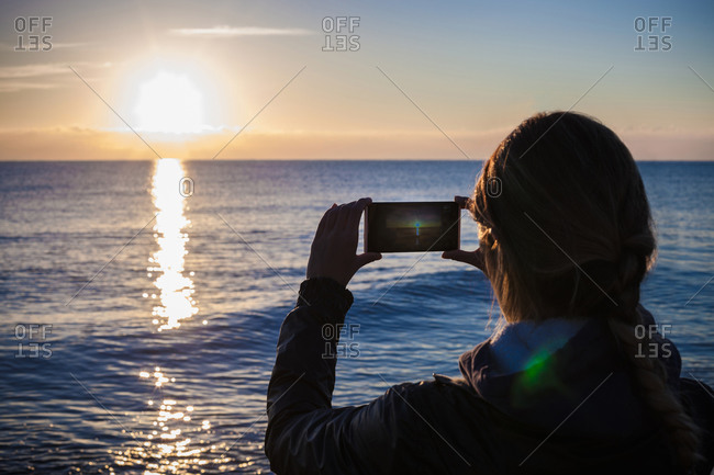 Over shoulder silhouetted view of young woman photographing sunset over sea, Villasimius, Sardinia, Italy