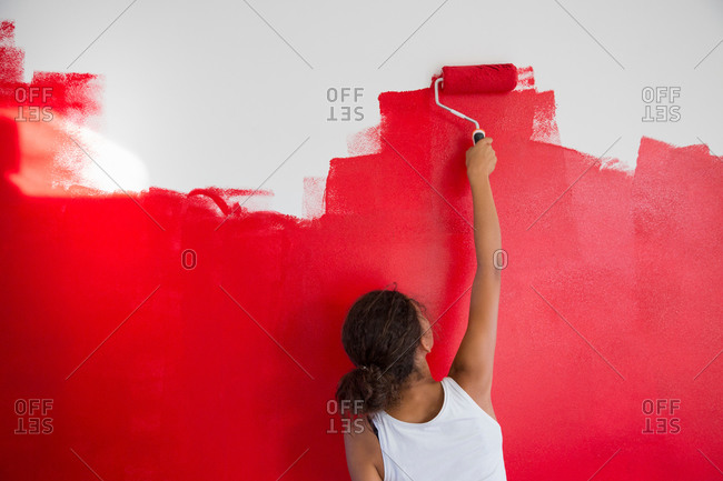 Rear view of girl painting red wall with paint roller