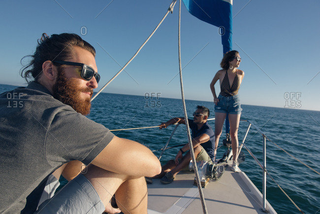 Friends looking out on the water on sailboat, San Diego Bay, California, USA