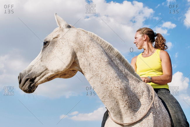 Low angle view of woman riding grey horse bareback against blue sky
