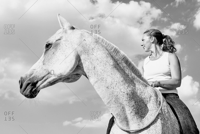 Woman riding grey horse against sky