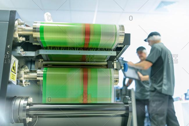 Workers at ink jet printer in food packaging printing factory