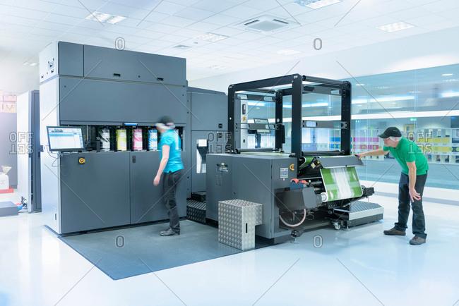 Workers with ink jet printer in food packaging printing factory