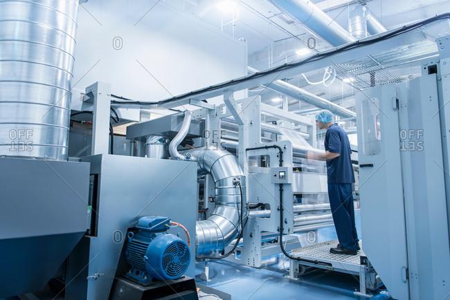 Worker operating printing machine in food packaging printing factory