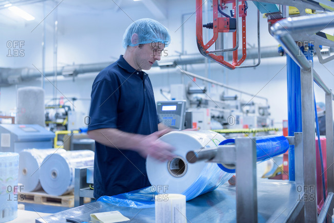 Worker moving roll of packaging in food packaging printing factory