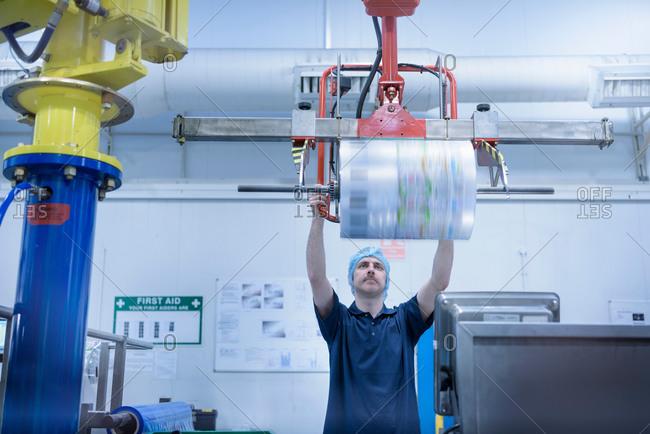 Worker lifting  roll of packaging in food packaging printing factory