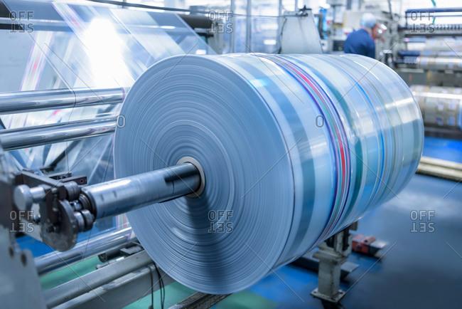 Spinning roll of printed packaging in food packaging printing factory