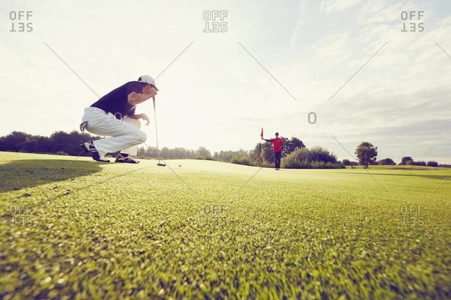 Golfer crouching on course, Korschenbroich, Dusseldorf, Germany