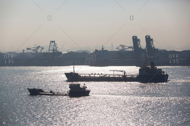 Container ships, cranes and containers at port in background