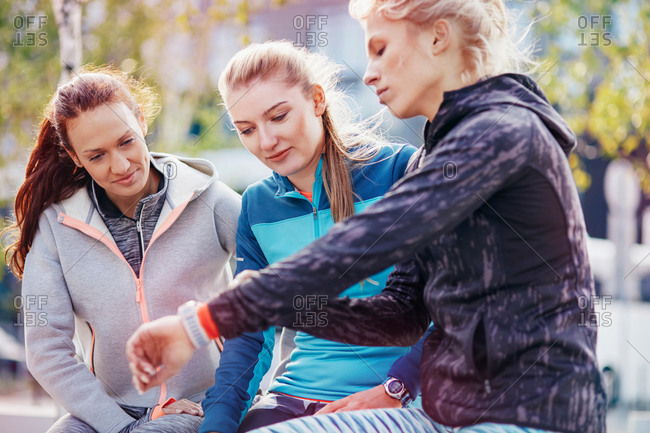 Three female runners coordinating times on smartwatch in city