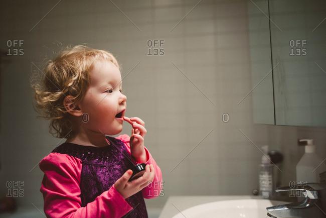 Cute girl looking in bathroom mirror applying lip gloss with finger
