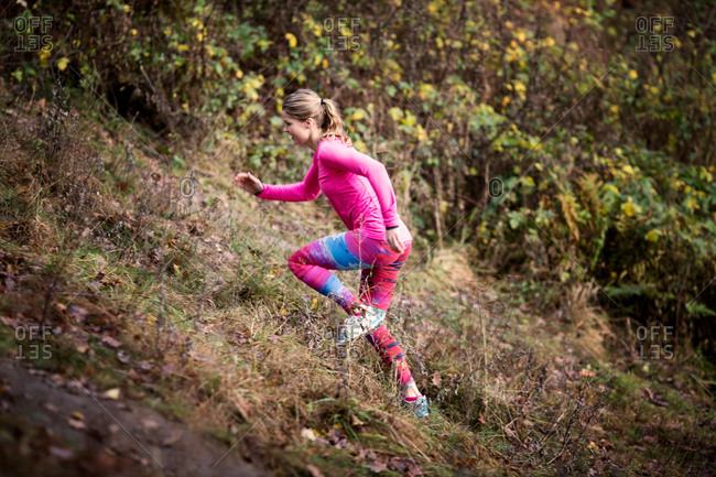 Side view of young woman wearing sport wear running up hill