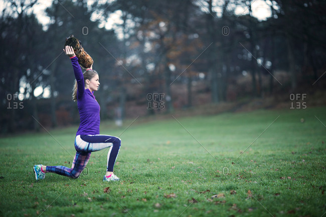 Full length side view of young woman arms raised holding tree branch doing lunge