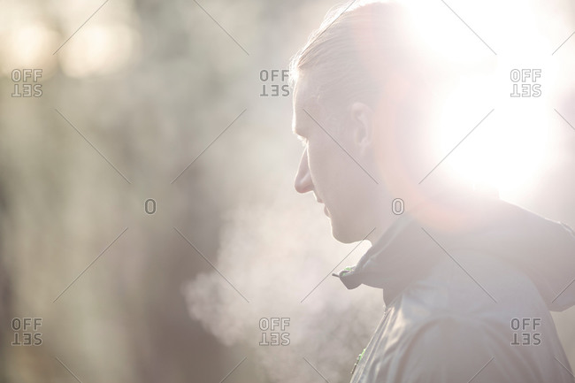 Side view of mid adult man looking away, condensation from breath