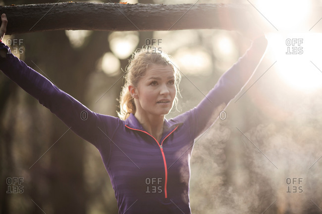 Young woman in forest arms raised holding tree branch, looking away, condensation from breath