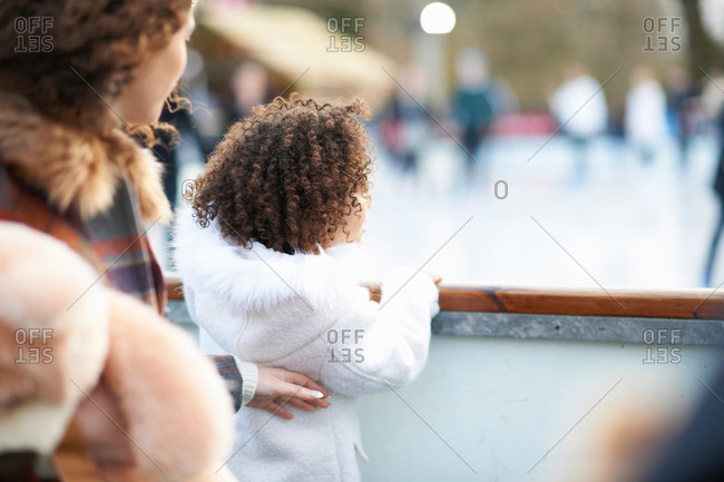 Rear view of mother and daughter watching people ice skating on ice rink