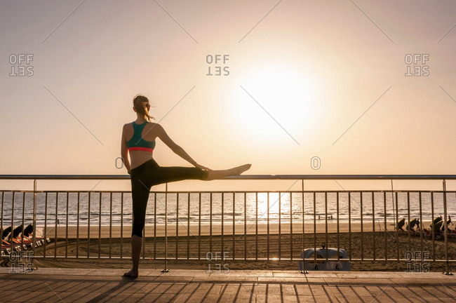 Rear view of mid adult woman on coastal path leg raised on railing looking away at view