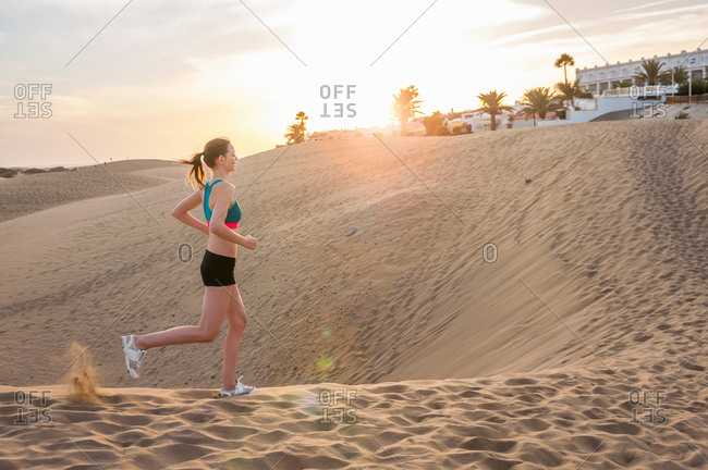 Full length side view of mid adult woman running across sand dune