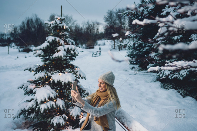 Young woman wearing woolen hat and scarf by illuminated Christmas tree using smartphone to take selfie smiling