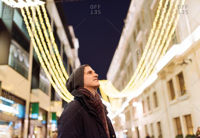 Young man looking up at xmas lights, London, UK