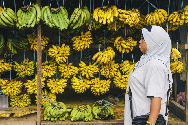 Woman in a Malaysian market looking at bananas