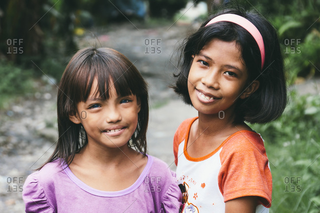 Filipino girls standing on a path and smiling