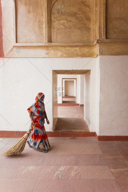 Woman carrying a large straw broom in the Tomb of Akbar, India