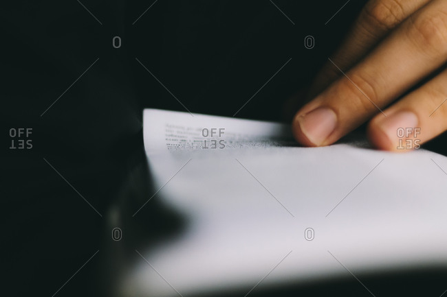 Close-up of a person's hand turning a book page